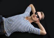Kühler blonder junger Mann, der an auf den Boden mit Sonnenbrille legt Lizenzfreies Stockfoto