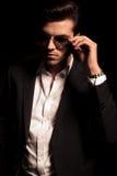 Kühler eleganter Mann hält seine Sonnenbrille Lizenzfreies Stockbild