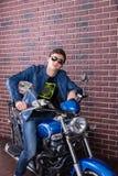 Kühler Geck, der auf seinem Motorrad sitzt Lizenzfreies Stockfoto