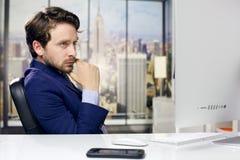 Kühler Geschäftsmann im Büro in New York, das PC schaut lizenzfreie stockbilder