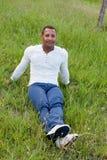 Kühler hübscher Kerl, der auf dem Gras sitzt Stockfotos