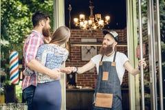 Kühler Herrenfriseur, der einem glücklichen Kunden einen Fauststoß an der Tür gibt stockfotos