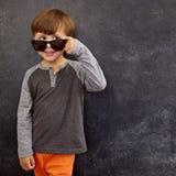 Kühler Junge, der über seiner Sonnenbrille am Kopienraum blickt Lizenzfreies Stockfoto