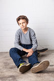 Kühler Junge, der auf seinem Skateboard sitzt Lizenzfreies Stockfoto
