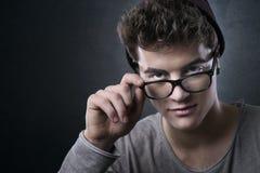 Kühler junger Mann, der seine Gläser justiert Stockbild