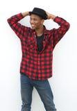 Kühler junger schwarzer Mann, der im karierten Hemd und im Hut aufwirft Stockfotografie
