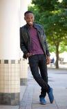 Kühler Kerl, der draußen in der schwarzen Lederjacke lächelt Stockfotografie