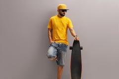 Kühler Kerl, der ein longboard hält Lizenzfreie Stockfotos