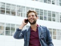 Kühler Kerl, der mit Mobiltelefon nennt Stockbilder