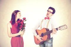 Kühler Kerl, der seine Frau mit einer süßen Serenade an einem Valentinsgruß ` s Tag gewinnt lizenzfreies stockbild