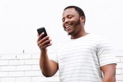 Kühler lächelnder junger schwarzer Mann, der Handy betrachtet Lizenzfreies Stockfoto