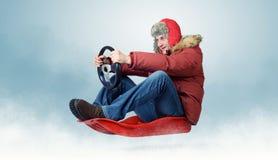 Kühler Mann auf einem Schlitten mit einem Lenkrad Stockfotografie