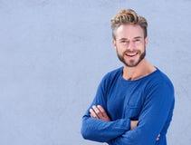 Kühler Mann mit Bart lächelnd mit den Armen gekreuzt Lizenzfreies Stockfoto