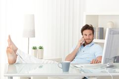 Kühler Mann mit Füßen oben auf Schreibtisch