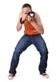 Kühler Mannphotograph mit Kamera in der Scharfschützehaltung Stockfotografie