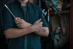 Kühler nobler junger Geck mit einer Tätowierung, die sich vorbereitet, sein bicycl zu reparieren lizenzfreie stockfotos