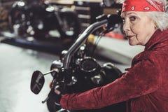 Kühler Rentner, der Fahrrad im Mechanikershop fährt lizenzfreie stockfotografie