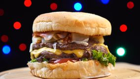 Kühler schöner frischer saftiger gekochter Burger drehen sich auf Drehscheibe gegen einen Hintergrund von bunten undeutlichen Lic stock video footage