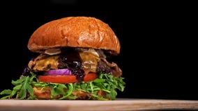 Kühler schöner frischer saftiger gekochter Burger drehen sich auf Drehscheibe Sehr köstliches Luftbrötchen und gemarmortes Rindfl stock footage