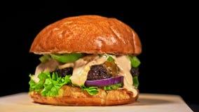 Kühler schöner frischer saftiger gekochter Burger drehen sich auf Drehscheibe Sehr köstliches Luftbrötchen und gemarmortes Rindfl stock video footage