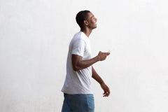 Kühler schwarzer Kerl, der mit Handy geht Lizenzfreie Stockbilder