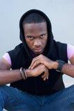 Kühler schwarzer Kerl, der mit Haubensweatshirt sitzt Lizenzfreie Stockbilder