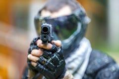 Kühler tireur mit Pistole im Paintballsturzhelm, der in camera zielt Lizenzfreie Stockfotos