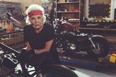 Kühler weiblicher Rentner, der nahe bei Motorrad findet stockfotografie