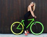 Kühles athletisches blondes Mädchen in der schwarzen sexy Ausstattung, die mit grünem hellem örtlich festgelegtem Fahrrad aufwirf Stockfoto