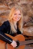 Kühles blondes Mädchen, welches die Gitarre im Freien spielt Lizenzfreie Stockfotografie