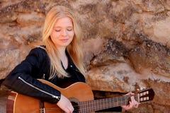 Kühles blondes Mädchen, welches die Gitarre im Freien spielt Lizenzfreie Stockfotos