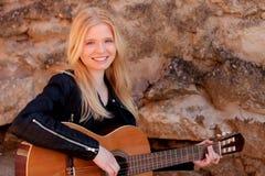 Kühles blondes Mädchen, welches die Gitarre im Freien spielt Lizenzfreie Stockbilder