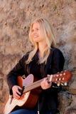 Kühles blondes Mädchen, welches die Gitarre im Freien spielt Lizenzfreies Stockbild
