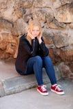Kühles blondes Mädchensitzen im Freien Stockfotografie