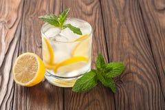 Kühles Getränk mit Zitrone und Minze auf einem hölzernen Hintergrund Lizenzfreie Stockfotografie