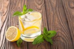 Kühles Getränk mit Zitrone und Minze auf einem hölzernen Hintergrund Stockfoto