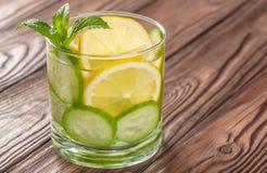 Kühles Getränk mit Zitrone und Minze auf einem hölzernen Hintergrund Stockbild