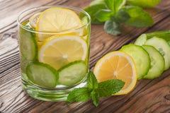 Kühles Getränk mit Zitrone und Minze auf einem hölzernen Hintergrund Stockfotografie
