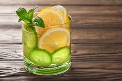 Kühles Getränk mit Zitrone und Minze auf einem hölzernen Hintergrund Lizenzfreies Stockbild