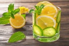Kühles Getränk mit Zitrone und Minze auf einem hölzernen Hintergrund Lizenzfreies Stockfoto