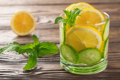Kühles Getränk mit Zitrone und Minze auf einem hölzernen Hintergrund Stockbilder