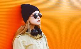 Kühles Hippie-Mädchen, das einen schwarzen Hut und Kopfhörer trägt Stockbilder