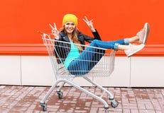 Kühles Mädchen der Mode recht im Laufkatzenwarenkorb, der den Spaß trägt schwarzen Jackenhut über bunter Orange hat Stockfoto