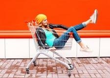 Kühles Mädchen der Mode recht im Laufkatzenwarenkorb, der schwarzen Jackenhut über bunter Orange trägt Lizenzfreie Stockfotografie