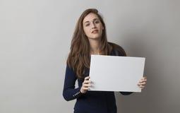 Kühles Mädchen 20s mit dem langen Haar, das eine Mitteilung auf weißem Hintergrund blockiert Stockfotos