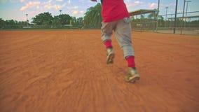 Kühles steadicam schoss vom Kind, das zur ersten Base auf Baseballfeld läuft Von hinten ihn geschossen stock footage