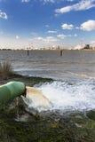 Kühlwasserrohr und Raffinerie in Fluss Lizenzfreie Stockfotos