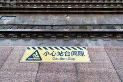 Kümmern Sie sich das um Abstandszeichen, das auf Bahnstation ` s Bahnsteigkante gemalt wird Lizenzfreie Stockfotografie