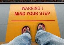 Kümmern Sie sich um Ihren Schritt Signage auf einer Zugplattform Lizenzfreies Stockbild