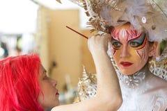 Künstler Applies Body Paint zum Gesicht des weiblichen Modells am Festival Stockfoto